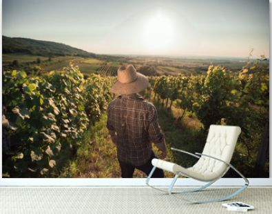 Satisfied farmer with hat standing in his vineyard