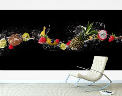 Pieces of fruit in water splash, isolated on black background