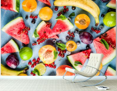Summer vitamin food concept, various fruit and berries watermelon peach mint plum apricots blueberry currant, creative flat lay on light blue background top view copy space