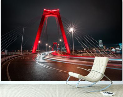 Light trails of traffic at the Willemsbrug in Rotterdam. Beautiful red bridge. Landmark of the skyline in Rotterdam, long exposure shot.