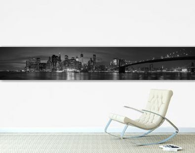 New York city with Brooklyn Bridge, iconic skyline panorama at night in black and white