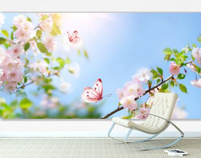 Beautiful pink butterfly and cherry blossom branch in spring on blue sky background, soft focus. Amazing elegant artistic image of spring nature, frame of pink Sakura flowers and butterfly.
