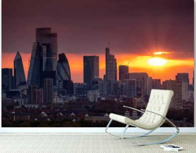 The skyline of the City of London with the modern office skyscrapers shining in the red sunset light