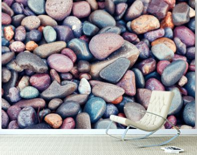 Top down closeup view of beautiful pastel colored wet pebbles at the seaside.