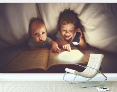 children brother and sister read a book with aflashlight under b