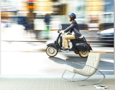 A man is riding a moped along the street