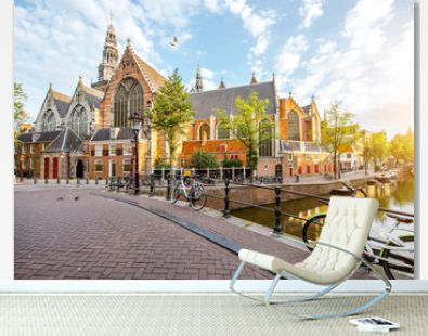 Morning view on the water channel with Old Church during the sunny weather in Amsterdam city