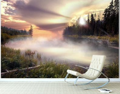 Spectacular colorful sunset sunrise landscape on a foggy lake with trees in yellowstone hot spring