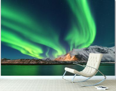 Aurora borealis. Lofoten islands, Norway. Aurora. Green northern lights. Starry sky with polar lights. Night winter landscape with aurora, sea with sky reflection and snowy mountains. Nature. Travel