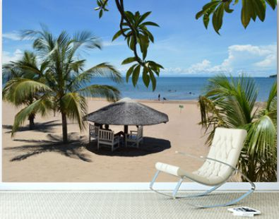 White wooden bungalow surrounded by palm leaves on the beach of amazing lake Malawi or Nyasa in Africa. Perfect peaceful sunny day on the beach of turqouise lake.