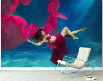 Girl mermaid. Underwater scene. A woman, a fashion model in the water in a beautiful dress swims like a fish.