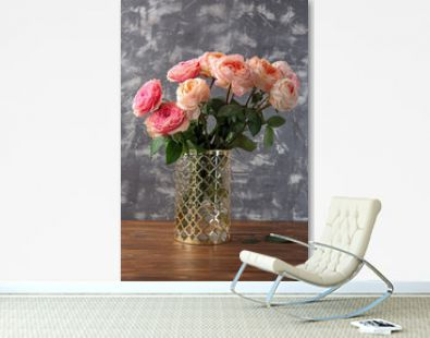 Vase with bouquet of beautiful roses on table against grey textured background