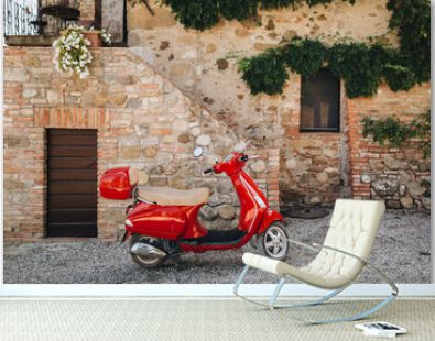 In the courtyard of an old house in Italy there is a red scooter