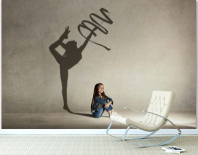Baby girl dreaming about gymnast profession. Childhood and dream concept. Conceptual image with shadow of female gymnast on the studio wall