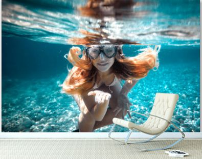 Beautiful woman with long hair underwater portrait in the tropical sea