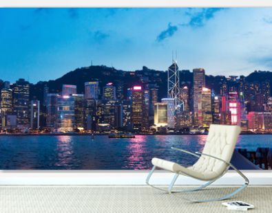 Hong Kong cityscape view of modern buildings over water from Victoria harbor at blue hour