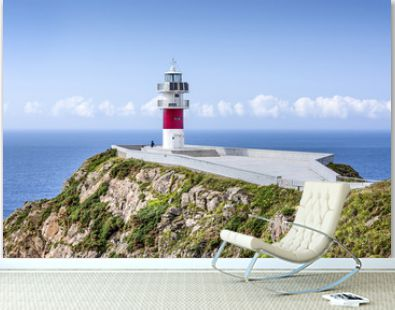 Spain, Cabo Ortegal: Seascape with beautiful red white striped lighthouse, people tourists, coastline, ocean sea water, cliff, skyline and blue sky in background - concept navigation. July 13, 2018