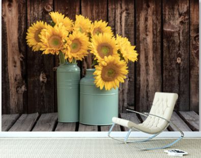 Two bunches of sunflowers in green buckets on a rustic plank table.