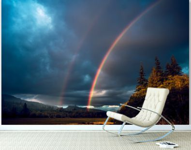 A rainbow coming down from stormy skies over the vast forests in the mountains of western Washington state USA