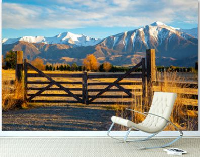 A closed wooden farm gate at the entrance to a farm in the high country below snowy mountains, Springfield, New Zealand