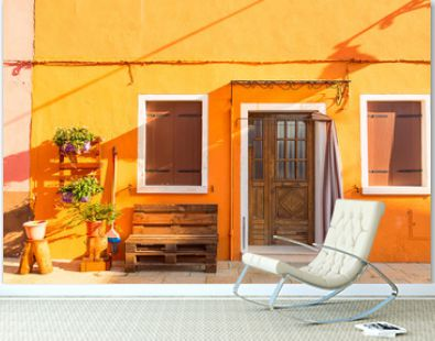 Yellow house with flowers and bench. Colorful houses in Burano island near Venice, Italy. Venice postcard. Famous place for european tourism and travel