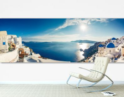 Churches in Oia, Santorini island in Greece, on a sunny day. Panorama view.