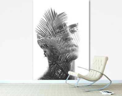 Double exposure of a young sexy man's portrait blended with branches of a tropical palm tree, showing the perfect beauty of nature's creation in black and white