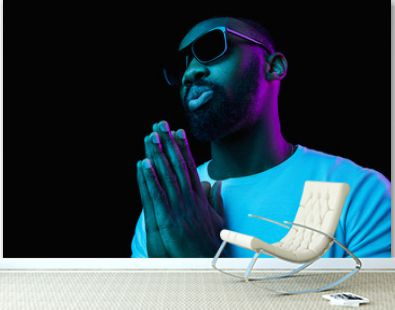 The retro wave or synth wave portrait of a young happy smiling african man in sunglasses at studio. High Fashion male model in colorful bright neon lights posing on black background. Art design