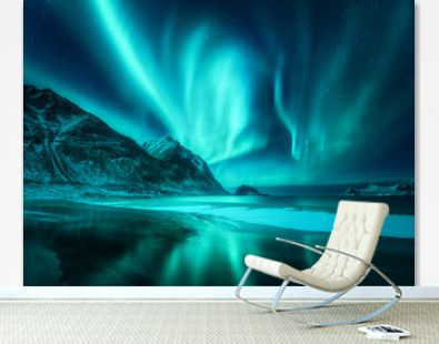 Amazing aurora borealis. Northern lights in Lofoten islands, Norway. Starry sky with polar lights. Night winter landscape with aurora, sea with frosty coast and sky reflection, snowy mountains. Travel