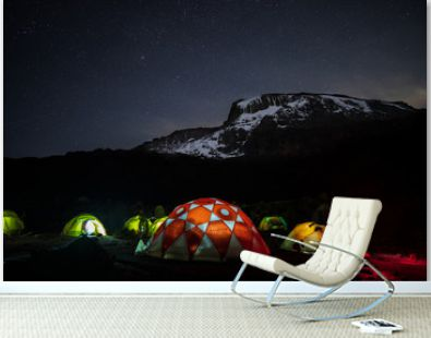 Lighted tents in the night in front of Mount Kilimanjaro