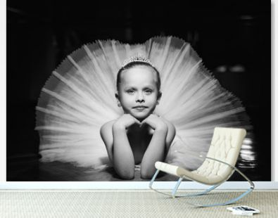 Black and white photo of a cute smiling ballerina in white tutu and a crown laying on the floor with hands under the chin. Beautiful little girl laying in nice tutu on the black background.