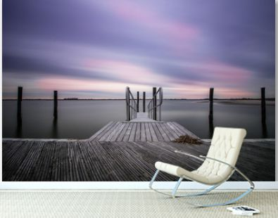 An empty peaceful dock within a marina as clouds streak across the sky. Still water, serene and calm scene
