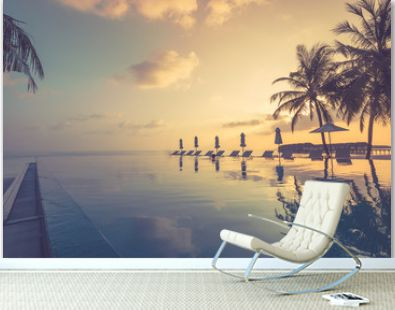 Amazing mood with poolside and palms next to beach and the ocean. Sunset sky and calm sea for luxury vacation tourism concept