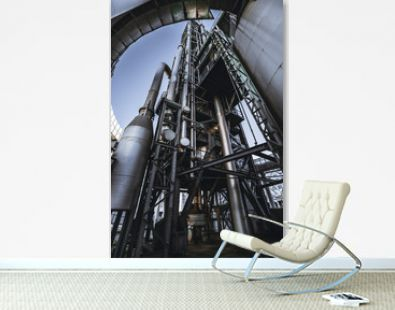 A wide-angle vertical view from the bottom of a modern oil refinery or a contemporary fuel factory facility in an industrial zone, with a round bridge, plenty of pipes, metal beams, tanks, and stairs