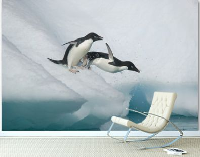 Adelie penguins leap from an iceberg in Antarctica