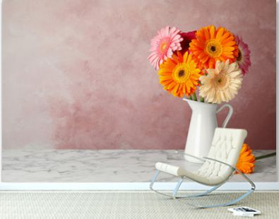 Bouquet of beautiful bright gerbera flowers in vase on marble table against color background