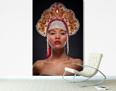 Fashionable portrait of a mulatto woman with the red lipstick on full lips. Studio shoot of an african american female model with the richly decorated kokoshnik on her head. Russian style, culture