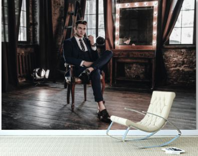 Fashion luxury man sitting on chair. Stylish businessman in full suit posing in interior room. Young handsome male model. Business concept. Success lifestyle