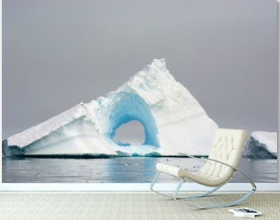 Antarctica. Charlotte Bay. Giant iceberg with a hole in the middle of it.