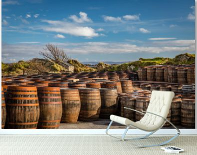 Rows of used whiskey barrels of graduating sizes sit in front of windswept coastal grassy hills below deep blue skies at Ardbeg Distillery in Scotland