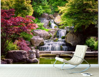 Waterfall long exposure with maple trees and bridge in Kyoto Japanese green Garden in Holland Park green summer zen lake pond water in London, UK