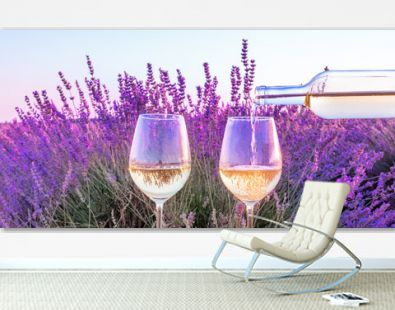 Lavender wine panorama. White wine poured from a bottle into glasses against a lavender field background