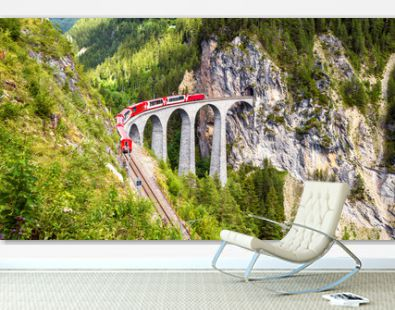 Landwasser Viaduct in Filisur, Switzerland. It is landmark of Swiss Alps. Red train of Bernina Express on high bridge in mountains. Panoramic view of famous railway.