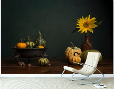 Still life with a sunflower, pumkins and a fruit bowl in a classical fine art image
