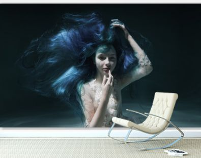 A beautiful girl with blue and long hair swims underwater in the pool in a fluffy white dress. Looks like a nymph or a mermaid
