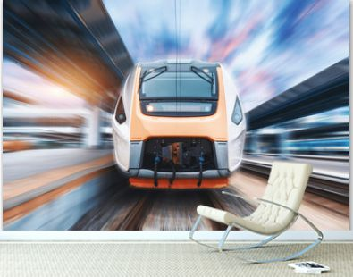 High speed train in motion on the railway station at sunset. Fast moving modern passenger train on the railway platform. Railroad with motion blur effect. Commercial transportation. Front view