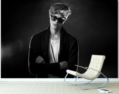 Trendy young man with cool hairstyle wearing black jacket with sunglasses. High Fashion male model posing on black background. Art design concept