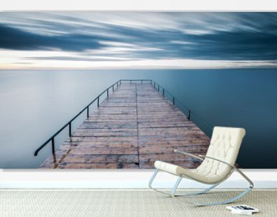 Empty wooden pier over blue sea with a sky background