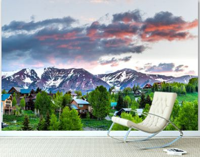 Cityscape of Crested Butte village small mountain town in Colorado in summer with dark morning sunrise clouds and chalet wooden houses on hills with green Aspen trees