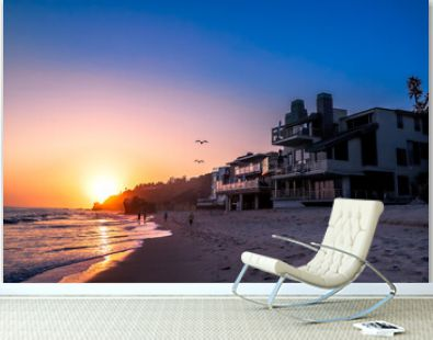 a stunning shot of the sunset at the beach with birds in flight in the sky, homes on the beach and people walking on the beach at El Matador beach in Malibu California